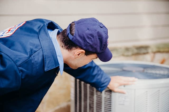 hvac technician inspecting an outdoor unit