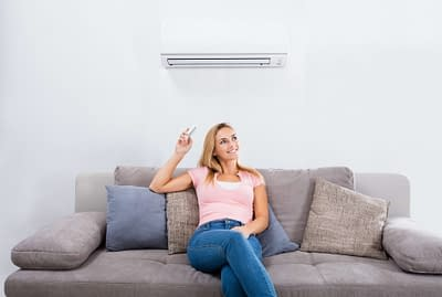 Woman Operating Air Conditioner With Remote Control