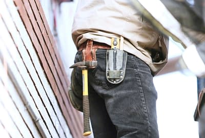 Technicians waist with a tool belt holding a hammer and other tools